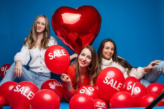 Happy pretty female friends sitting with sale red air balloons, isolated on blue wall