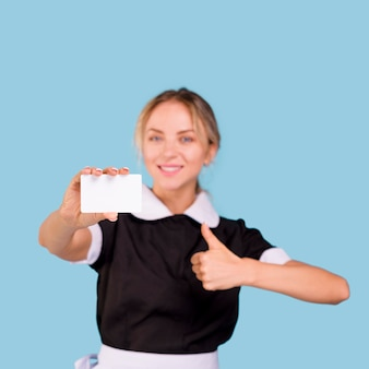 Happy pretty female janitor showing blank visiting card and thumb up gesture