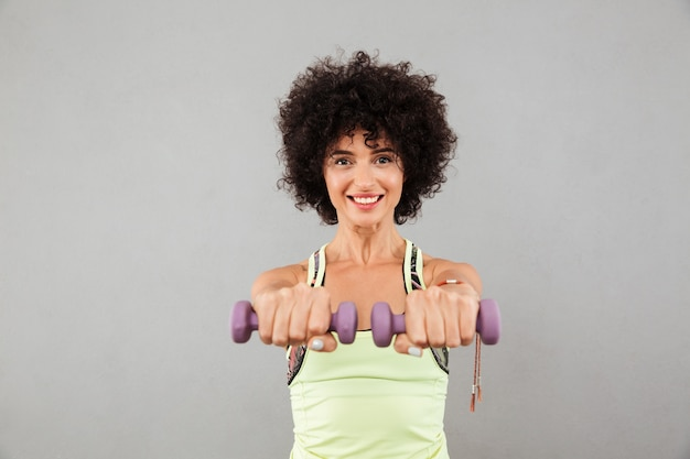 Happy pretty fitness woman doing exercise with dumbbells