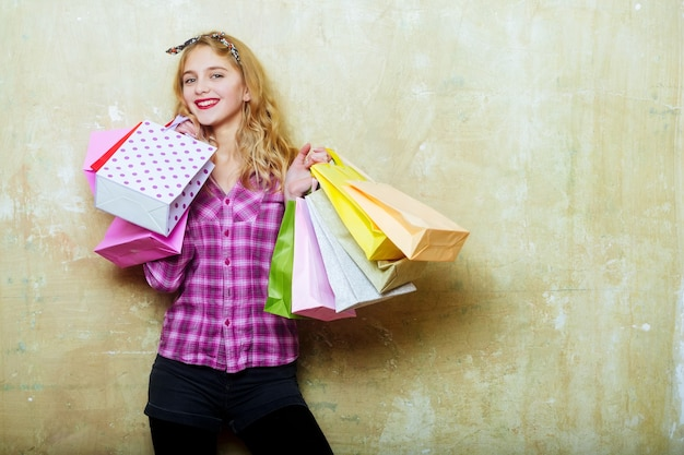 Happy pretty girl or beautiful woman with red lips and blond curly hair in stylish headband and violet plaid shirt smiles with colorful shopping bags in hands on beige wall background, copy space