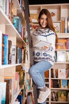 Happy pretty girl choosing book from book shelf in library