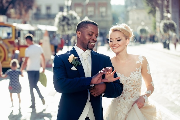 Happy pretty girl or cute bride with beautiful blond hair in white sexy wedding dress and handsome man or african american groom walking outdoors on sunny day on blurred city street background