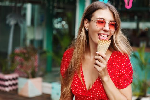 Счастливая красивая девушка ест мороженое и улыбается