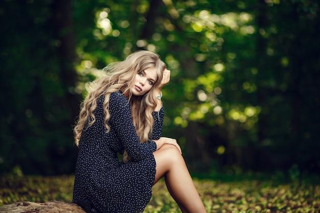 日没時のフィールドで幸せなかわいい女の子。