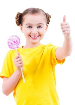 Счастливая красивая девушка в желтой футболке с цветными конфетами показывает палец вверх знак - изолированные на белом