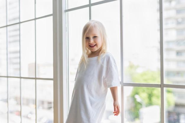 Happy pretty girl wearing blank white dress near big window