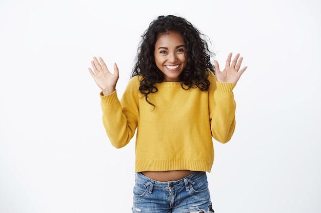 흥분과 행복을 보여주는 곱슬 머리를 가진 행복한 예쁜 소녀, 친구 인사, 손바닥을 흔들며 인사, 안녕 제스처, 마침내 새로운 노란색 스웨터 가을 쌀쌀한 날을 입을 수 있습니다