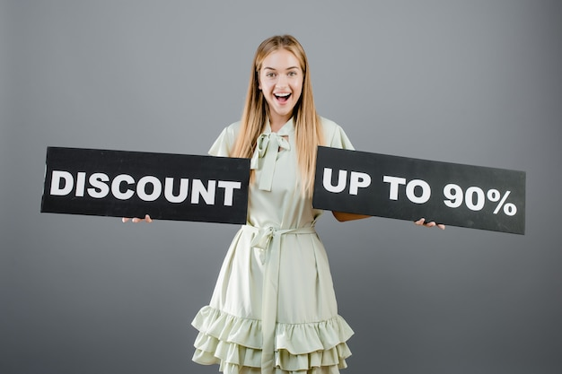 Happy pretty girl with discount up to 90% sign isolated over grey