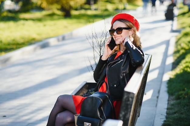街で電話の会話を楽しんで幸せなきれいな女性