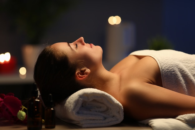 Happy pretty lady lying down on massage bed in wellness center. beauty concept