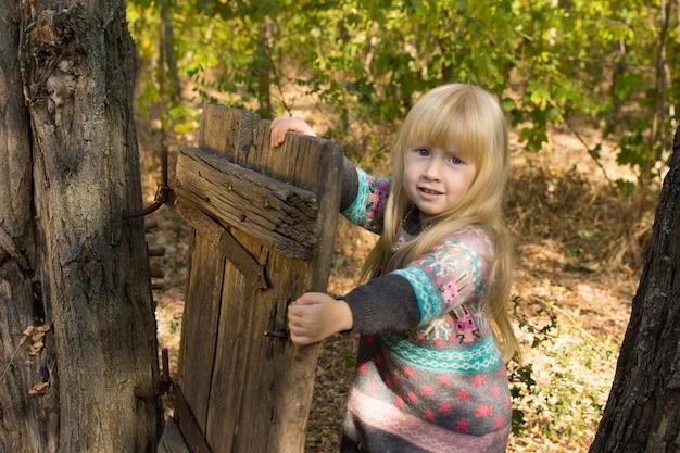 카메라를 보며 웃고 있는 동안 나무 줄기에 부착된 소박한 나무 문을 가지고 노는 행복한 금발 소녀