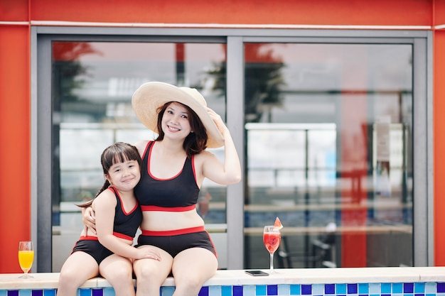 Happy pretty little girl hugging her mother in big straw hat when they are resting at swimming pool of spa hotel