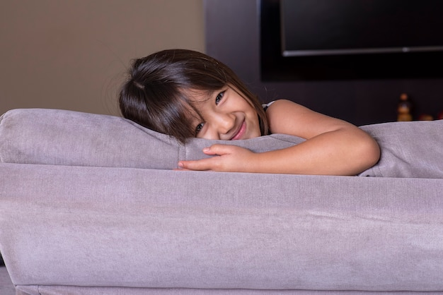 Счастливая милая маленькая девочка, играющая на диване