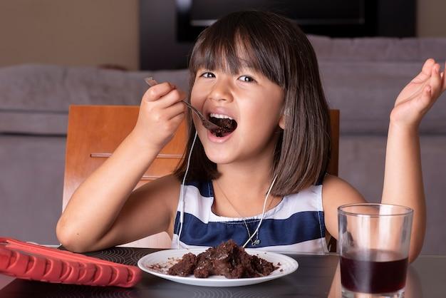 태블릿을보고 초콜릿 케이크를 먹는 행복 한 예쁜 소녀