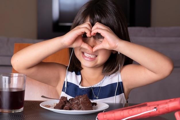 Счастливая милая маленькая девочка смотрит планшет и ест шоколадный торт