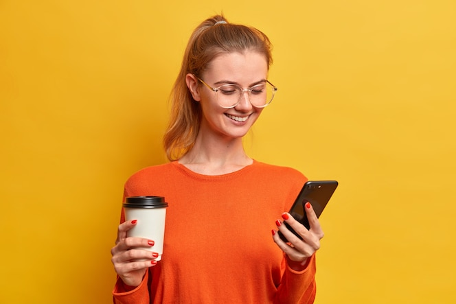 Happy pretty millennial girl downloads new mobile application, drinks coffee from paper cup, has pleasant smile, texting in chat, wears optical glasses, has combed hair in pony tail, surfs internet