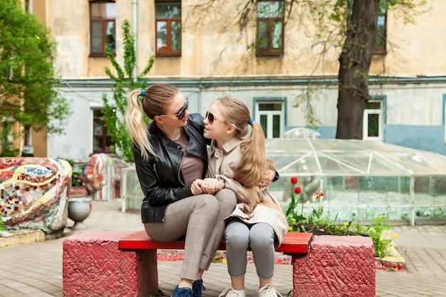 幸せなかわいい母親と庭の家の近くのベンチでカジュアルな服を着た小さな彼女のかわいい娘。子供や家族と一緒に素敵な関係を過ごすというコンセプト。サイトのコピースペース