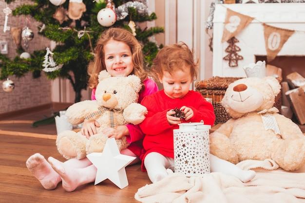 クリスマスの装飾が施された部屋に座っている幸せなかわいい姉妹