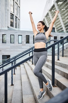 Happy pretty slim female in sportwear is standing on stairs to urban stadium and raising hands with joy