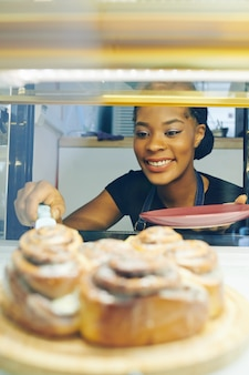 Happy pretty smiling black waitress taking cinnamon bun from showcase to serve for customers