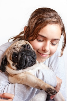 Happy pretty smiling teenager girl hugging pug dog with love