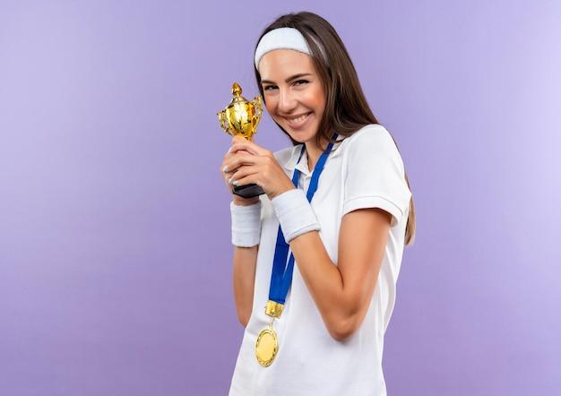 Felice bella ragazza sportiva che indossa fascia e braccialetto e medaglia che tiene tazza isolata sulla parete viola con spazio copia
