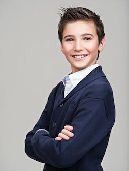 ファッションモデルとしてスタジオでポーズをとって幸せなかわいい10代の少年。