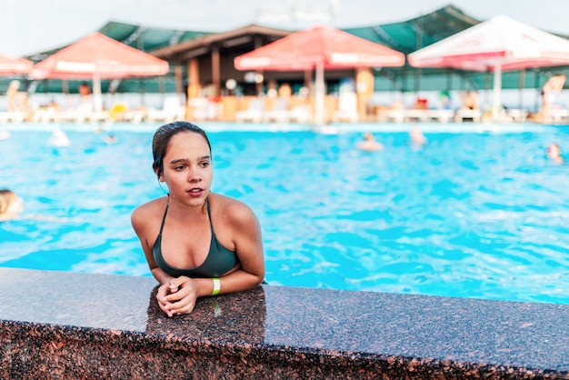 Happy pretty teenage girl emerged from the pool with clear blue water on a sunny warm summer day at the hotel during the holidays. concept restoration of health and relaxation of children after school