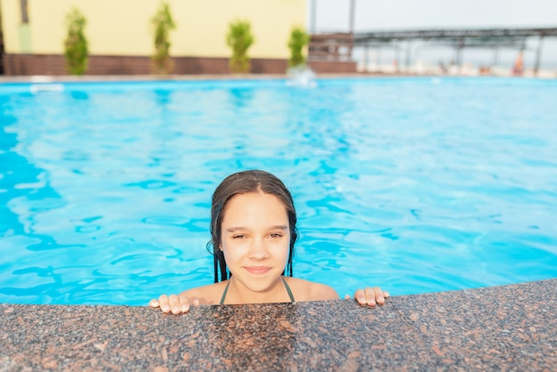 幸せなかわいい10代の少女は、休暇中にホテルで晴れた暖かい夏の日に澄んだ青い水でプールから現れました