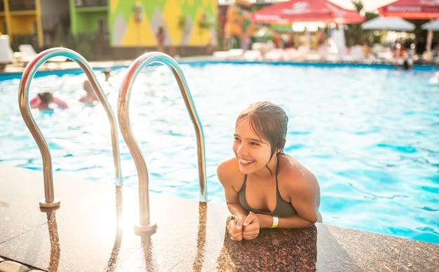幸せなかわいい10代の少女は、晴れた暖かい夏の日に澄んだ青い水でプールから現れました
