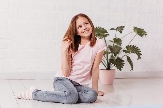 Счастливая красивая девочка-подросток сидит в белой комнате и мечтает