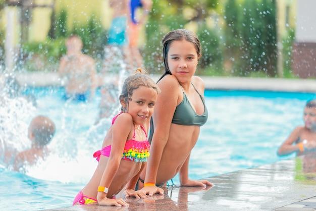 Счастливые симпатичные девочки-подростки вышли из бассейна с чистой голубой водой в солнечный теплый летний день
