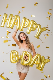 Happy pretty woman celebrating birthday in golden confetti