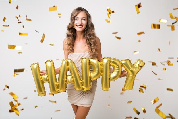 Happy pretty woman celebrating new year in golden confetti