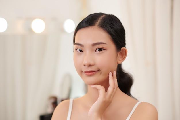행복 한 예쁜 여자는 건강하고 부드러운 보습 수분 피부, 얼굴 스킨 케어 회춘 수분 스파 매일 치료 개념을 즐길 수