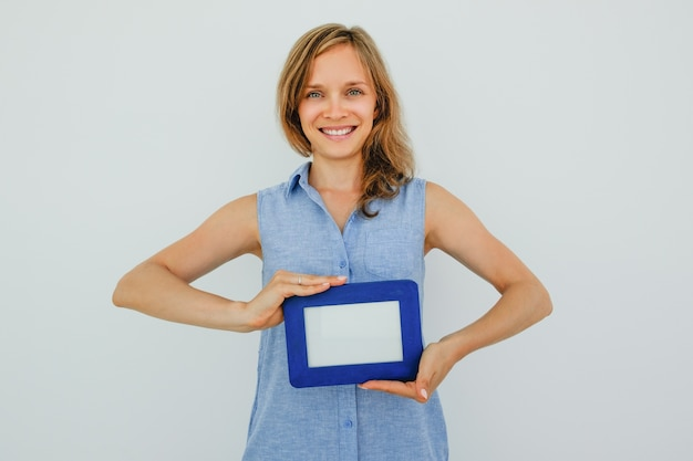 Happy pretty woman holding blank picture frame