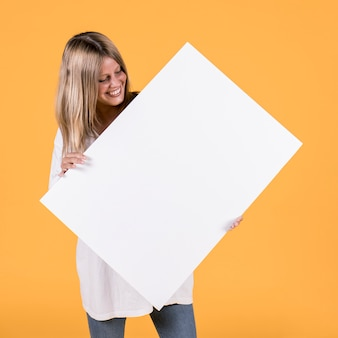 Happy pretty woman holding blank white cardboard against yellow wallpaper