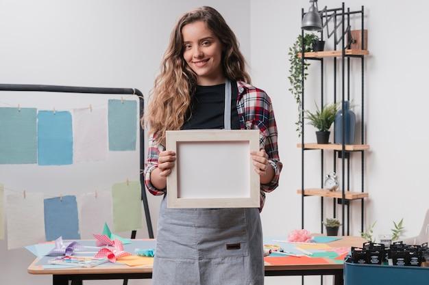 Happy pretty woman holding blank white photo frame