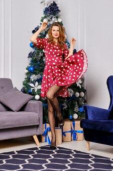점선으로 된 실크 드레스와 크리스마스 트리 주위를 돌고있는 폴카 도트 스타킹의 행복한 예쁜 여자