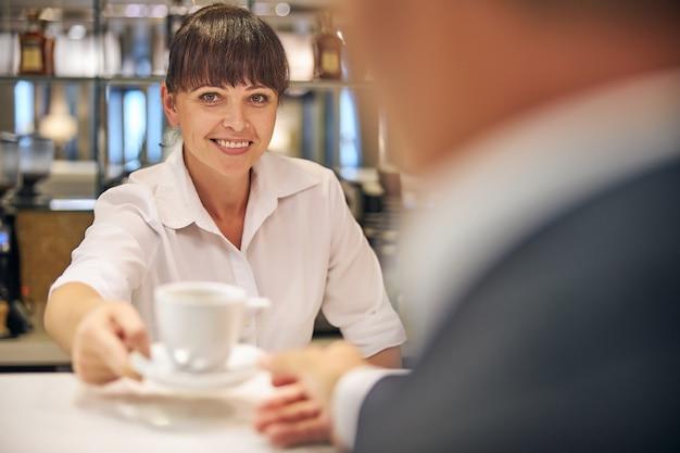 행복한 예쁜 여자가 바에서 일하고 우아한 남자에게 커피 한 잔을 대접하고 있다