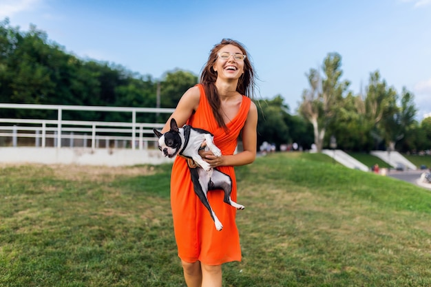 ボストンテリア犬を保持している幸せなきれいな女性公園、前向きなムードの笑顔、トレンディな夏のスタイル、オレンジ色のドレス、サングラス、ペットと遊ぶ、楽しんで、カラフル