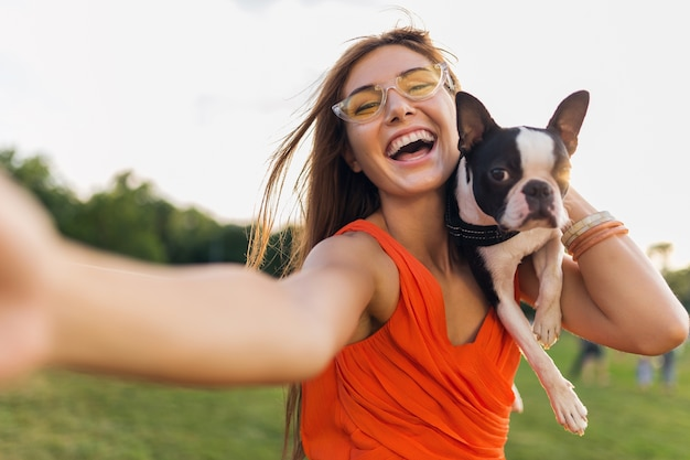 Happy pretty woman park making selfie photo, holding boston terrier dog, smiling positive mood, trendy summer style, wearing orange dress, sunglasses, playing with pet, having fun