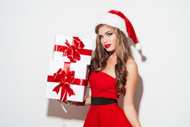 Happy pretty woman in red santa claus dress and hat holding gift boxes isolated