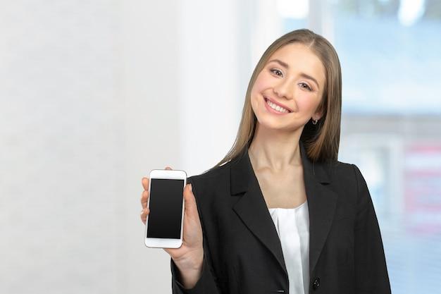 Happy pretty woman showing a blank smart phone screen