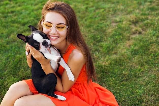 Felice bella donna seduta sull'erba nel parco estivo, tenendo il cane boston terrier, baciare, indossare un abito arancione, stile alla moda, giocando con animali domestici