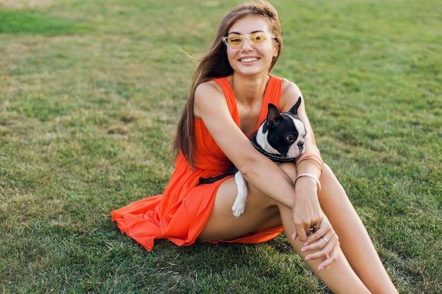 Счастливая красивая женщина, сидящая на траве в летнем парке, держа в руках собаку бостон-терьера, улыбаясь позитивным настроением, в оранжевом платье, модном стиле, играя с домашним животным