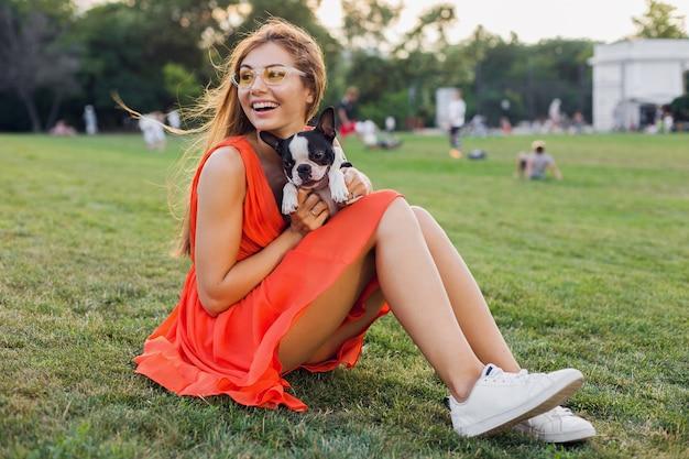 Счастливая красивая женщина сидит на траве в летнем парке, держит собаку бостон-терьера, улыбается позитивным настроением, в оранжевом платье, в модном стиле, стройные ноги, кроссовки, играет с домашним животным, развлечение на выходных