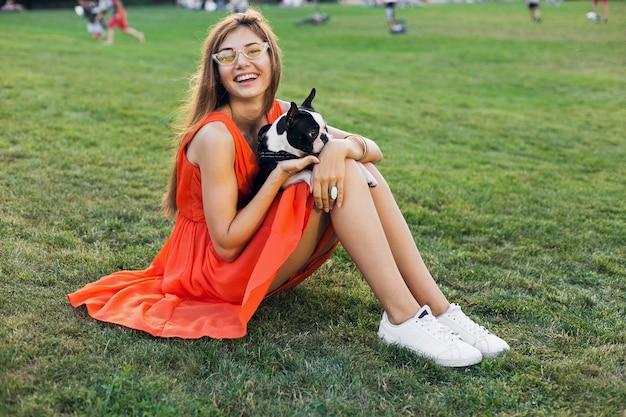Счастливая симпатичная женщина, сидящая на траве в летнем парке, держа собаку бостон-терьера, улыбаясь позитивным настроением, в оранжевом платье, в модном стиле, стройные ноги, кроссовки, играя с домашним животным