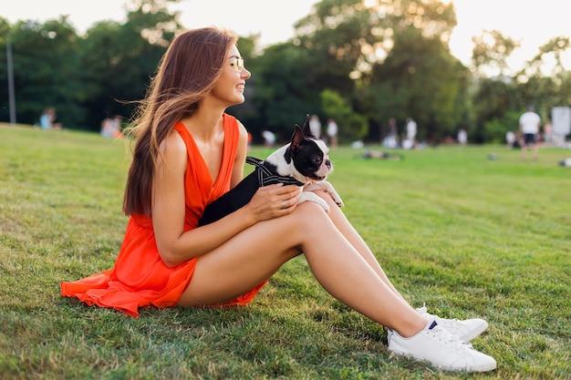 サマーパークの芝生に座って、ボストンテリア犬を抱いて、前向きな気分を笑顔、オレンジ色のドレスを着て、トレンディなスタイル、スリムな脚、スニーカー、ペットと遊ぶ幸せなきれいな女性