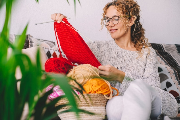 Счастливая симпатичная женщина улыбается и восхищается ее трикотажной работой с красной красочной шерстью. женщинам нравится заниматься вязанием в домашних условиях зимой.